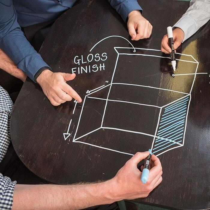 Smart wall paint being used to design packaging on black desk