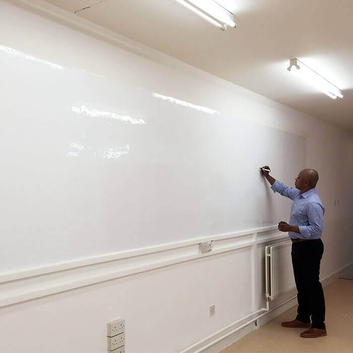 Man writing on glossy Smart Whiteboard Wallpaper